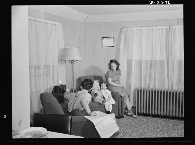 Bantam, Connecticut. Defense homes. Fred Heath works on the night shift at the Warren McArthur plant in Bantam, and spends his days with Mrs. Heath and their three-year-old daughter, Ann. Here they are in the living room of the Heath's new four-room apartment, part of the new eighty-unit defense housing project just five minutes walk from the plant. The Heaths, who pay thirty dollars rent, like overstuffed chairs, and Ann also likes her overstuffed Teddy Bear