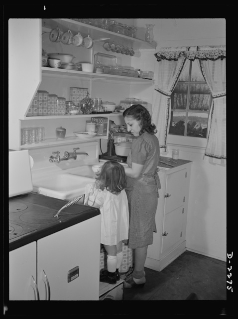 Bantam, Connecticut. Defense homes. Little Ann Heath is eager to try out all the facilities of her parents' new four-room defense housing unit, after spending most of her life in a single furnished room. Here she pushes her footstool to the sink in order to help her mother clean up the dinner dishes. Mrs. Heath, a native of Winsted, a city some twenty-five miles away, is delighted with her new kitchen--the first she's ever had which she actually considers as a kitchen, and is trying out all the recipes she has collected in five years of married life. The Heaths pay thirty dollars monthly for their apartment