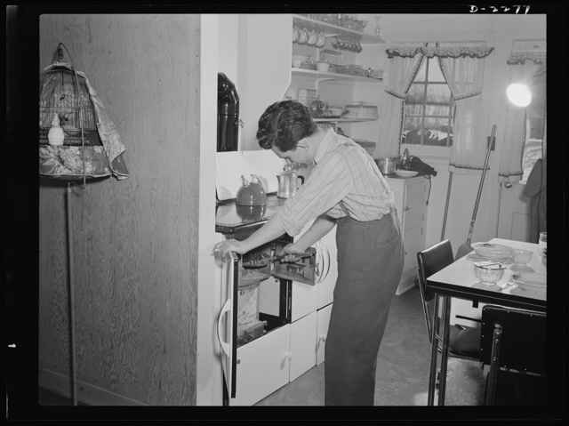 Bantam, Connecticut. Defense homes. The heating unit is in the kitchen of Fred Heath's four-room apartment in the new federally-financed homes for eighty families just a few minutes from the Warren McArthur factory in Bantam. The well-insulated coal fire puts steam in the radiators and provides the heat for cooking. The tenants are well-pleased although on several nights when the temperature dropped to ten degrees below zero they were forced to replenish the fuel every two or three hours. That cigarette Fred Heath holds is not tailor-made, by the way--he likes to roll his own