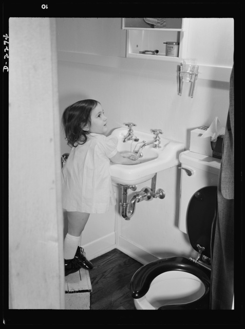 Bantam, Connecticut. Defense homes. Three-year-old Ann Heath, daughter of Fred Heath who operates a turret lathe in the Warren McArthur casting room. She has her own little footstool so that she can wash her own hands in the sink of the bathroom in the four-room defense housing unit where the Heaths live. Ann had quite a trying time getting used to the size of the new apartment, after having lived most of her life with her parents in a single furnished room in Torrington