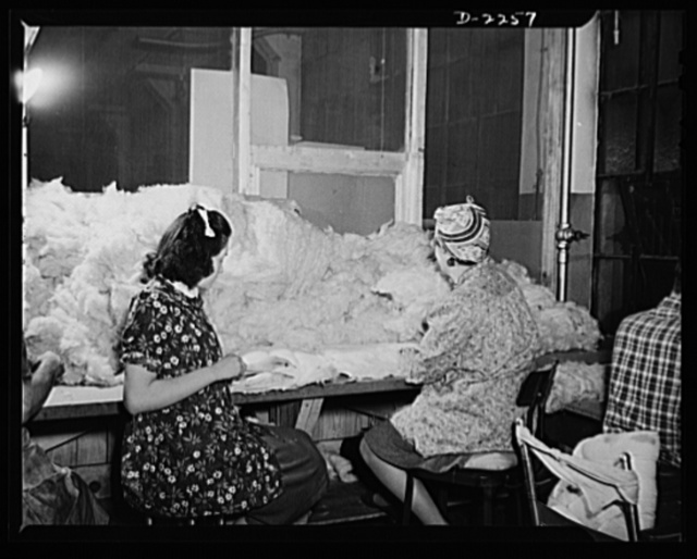 """Bantam, Connecticut. The kapok room in the Warren McArthur upholstery shop is screened off to prevent the feathery filling from flying freely about the plant. Expert at stuffing kapok into cushions are Barbara Skilton and Frances Humphrey. Barbara, at left, lives in Morris, the next town to Bantam, at her father's farm, where several other workers in the plant board. Her husband works at the Waterbury Brass Company, and they have a son two years old. Frances, a graduate of Litchfield High School, prefers this work to the secretarial position she used to have in Torrington. """"There is more money, and you don't have to worry about it at night,"""" she says. Both girls began work in Bantam in December, 1941"""