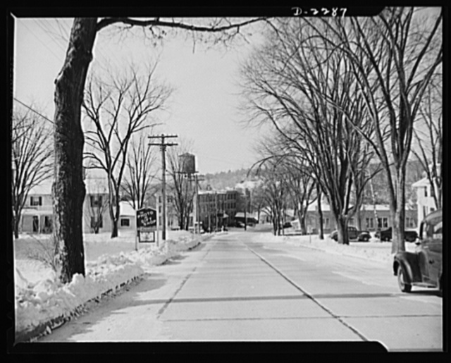 """Bantam, Connecticut. Tree-lined Lafayette Boulevard--Route 25 to the motorist passing through Bantam--is the """"main stem"""" of the town. The """"Photo and Gift Shop,"""" directly opposite the post office, is open all year, although its real business is done during the summer; at that season Bantam and the nearby town of Morris are host to some 350 vacationers at Bantam Lake, which is mainly in Morris. Below the shop is the office of Bernard C. Roeberg, the town's leading real estate dealer who is also principal of the Bantam School, a corner of which may be seen to the right. The large building with the water tower at the bottom of the hill is the Connecticut Electric Company, which has not yet started to enjoy the increased business brought to Bantam by the war program. Opposite this plant is a brick building used by the state highway department for storage. A section of this building is devoted to a small shop employing, at most, six people. Here bathrobes are occasionally turned out. No one was seen in the shop during the ten days the OEM (Office of Emergency Management) crew was in Bantam, although there was always a bunch of keys hanging in the locked door"""