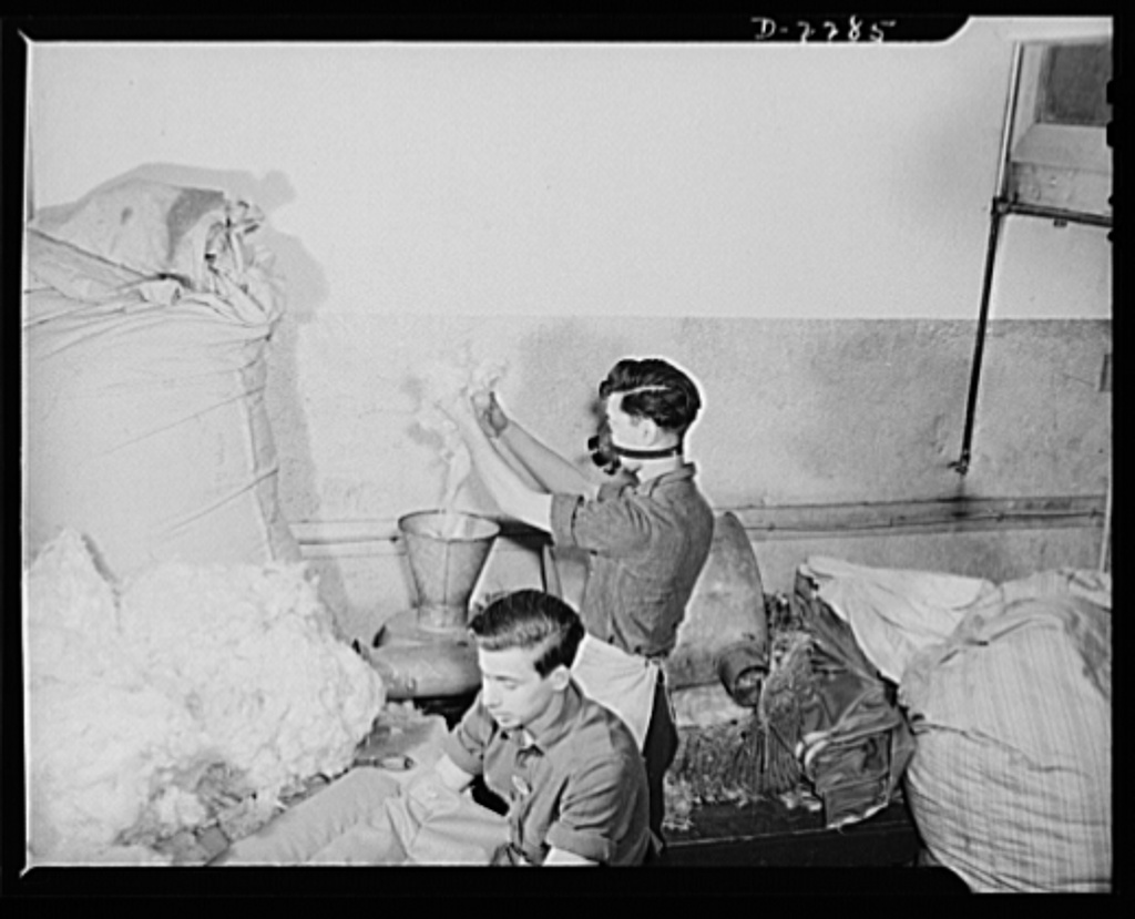 Bantam, Connecticut. While Patsy DiGiovanni puts kapok through the filler machine, which fluffs it out, Chet Wash is stuffing the back cushion of bomber pilot's seat in the upholstery shop of the Warren McArthur Corporation. Patsy came to work here in April 1941, from his native Torrington, where he had been driving a taxicab. He still lives in Torrington. Wash learned upholstery on a NYA (National Youth Administration) project in his native town of Plains, Pennsylvania. He's been in Bantam since June 1941, living in a furnished room
