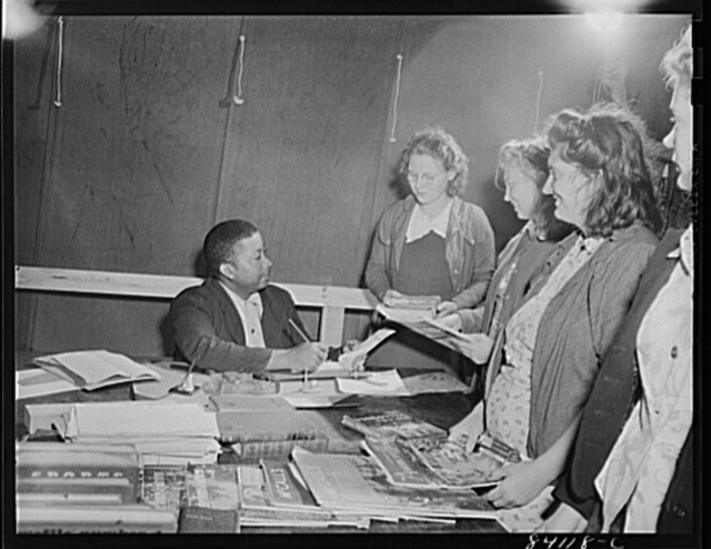 Batavia, New York. Elba FSA (Farm Security Administration) farm labor camp. Recreational director signing out books from the camp library to newly-arrived high school girls from Richwood, West Virginia.