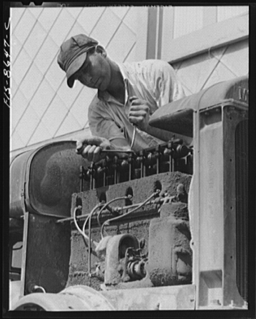 """Beltsville, Maryland. Employees of the United States Department of Agriculture experimental farm demonstrating the care and repair of farm machinery for posters to be used in a """"Share and Repair"""" conservation program"""