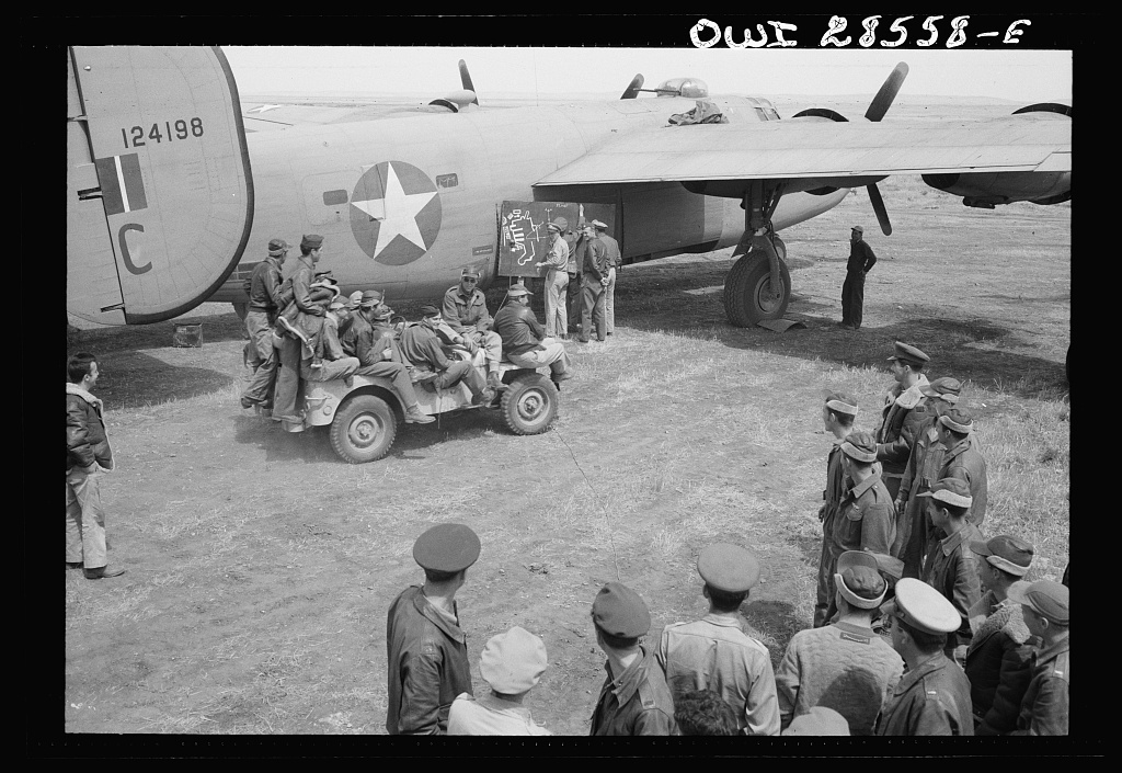 Bomber crews of the United States Army Ninth Air Force are given a chalk talk before they take off on a mission over Axis Territory. These are some of the heavy bonber groups which are disrupting Axis shipping in the Mediterranean. Giving the blackboard talk is Major Frank W. Delong, squadron commander.