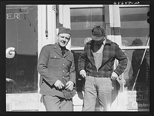 Bowdle, South Dakota. Soldier home on furlough, talking with friend in front of pool hall