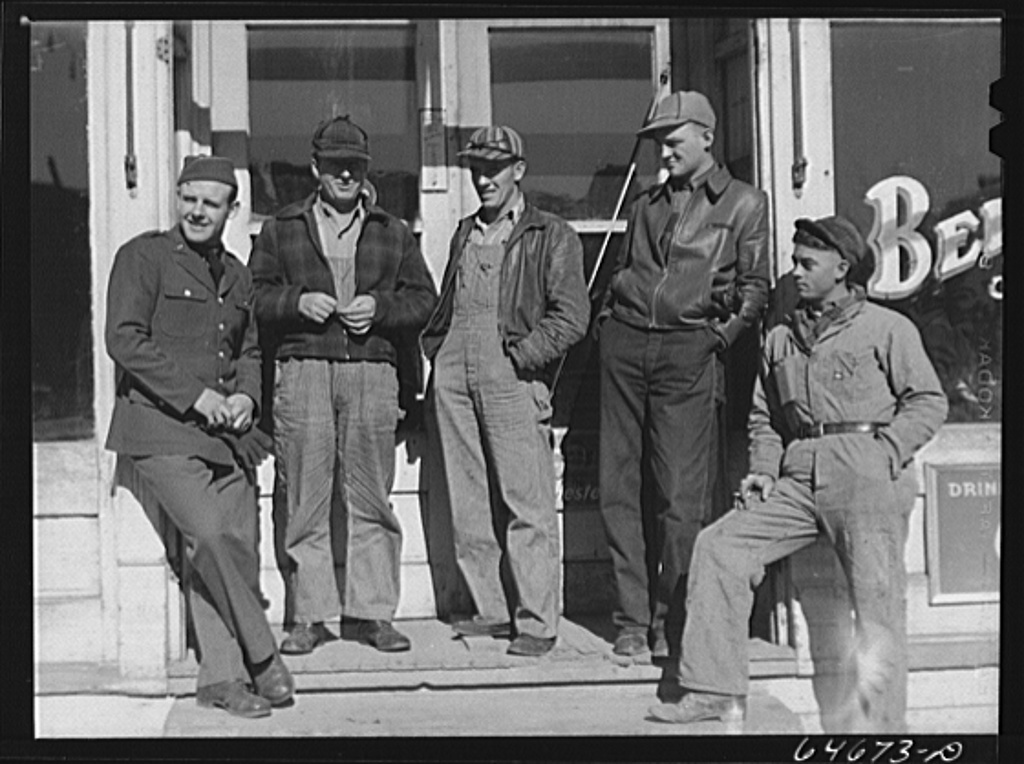 Bowdle, South Dakota. Soldier on furlough with friends in front of pool hall