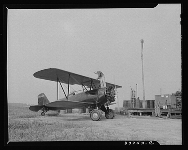 Bridgeton, New Jersey. Seabrook Farm. Delivering gasoline to plane, at dawn, for dusting fields. Dust or insecticide is spread by low flying planes onto crops to control various insect pests
