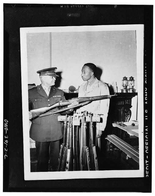 Brigadier General Benjamin O. Davis explaining the operation of a rifle to a U.S. Negro trooper somewhere in England