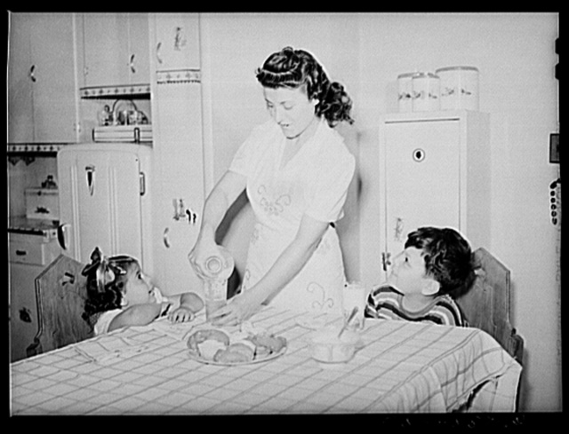 Brooklyn, New York. Red Hook housing development. Mrs. James Caputo in the modern kitchen of her apartment, pouring milk for Annette and Jimmy. The children drink more than a quart apiece daily