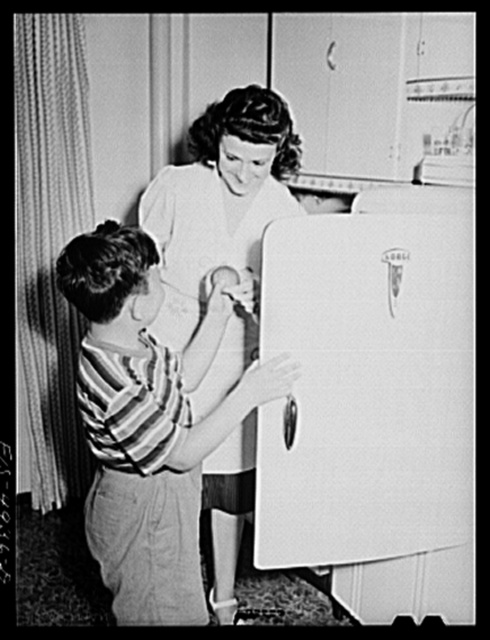 Brooklyn, New York. Red Hook housing project. Mrs. Caputo giving her son Jimmy an apple from the refrigerator