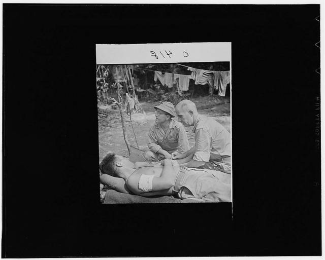 Buna, New Guinea. A wounded man behind the lines on the Buna front being given a blood transfusion. Lieutenant J.J. Gotow, of Flint, Michigan, is assisting Captain W.F. Edwards, of New Albany, Indiana