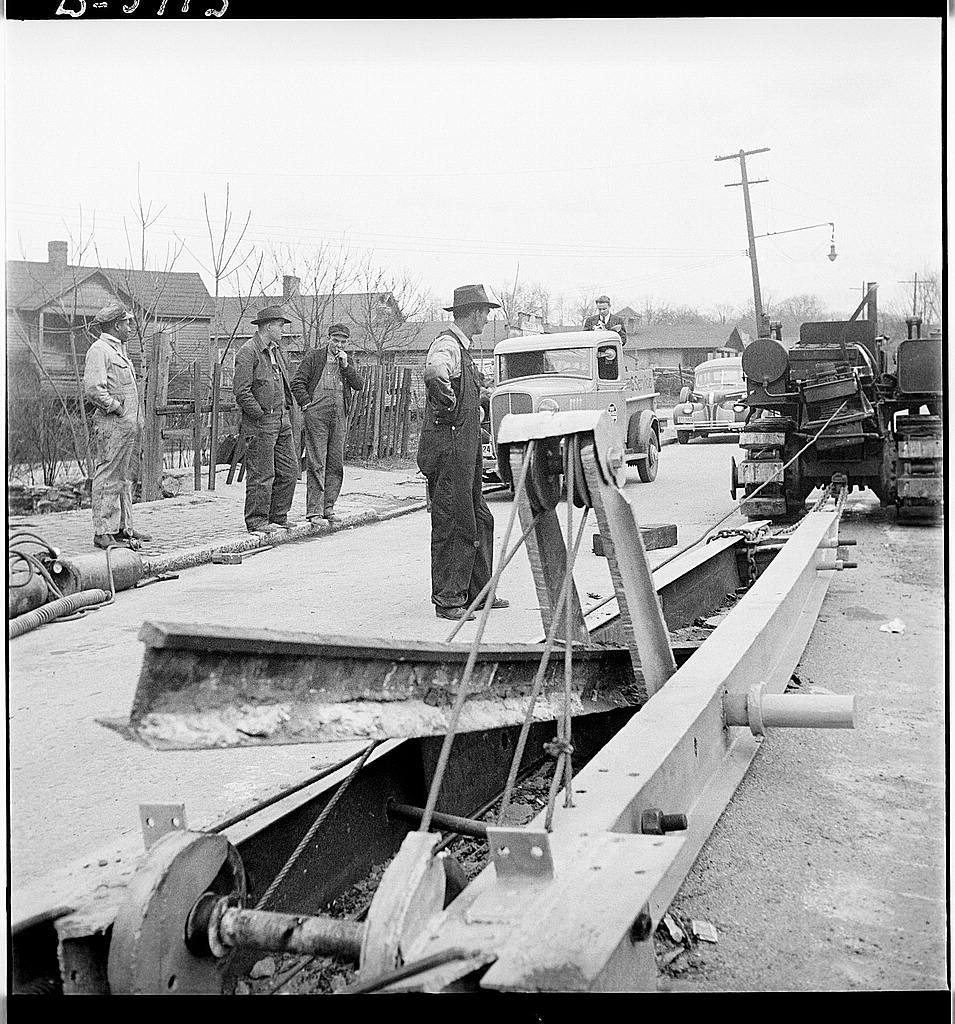 "Buried trolley tracks salvaged to aid war program. Removing abandoned trolley tracks to provide much needed scrap for Uncle Sam. Here, in Asheville, North Carolina, a local inventor demonstrates his ""railjerk"" for doing the trick. He claims his device, employing three men, can pry loose a mile of track a day"