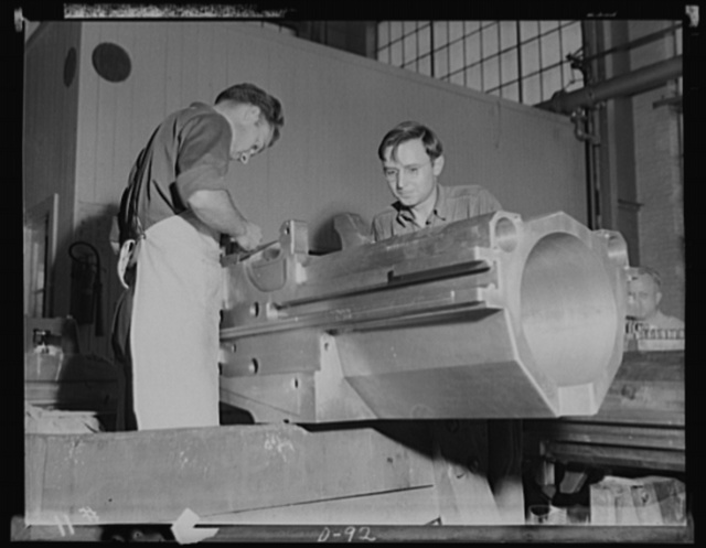 Business district. Bench workers finishing a breech housing for a medium caliber gun in a large eastern arsenal. This is a section of the business part of one of the guns being turned out for the war production program