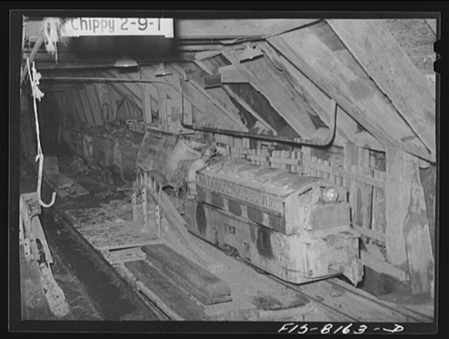 Butte, Montana. Anaconda Copper Mining Company. Dumping train of copper ore cars into hopper from which the ore will be lifted to the surface