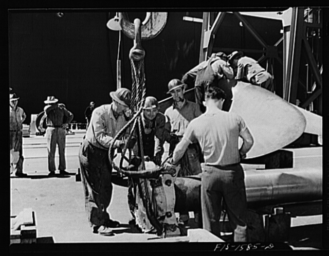 California Shipbuilding Corporation, Wilmington, California. Workmen attaching a hoist to a section of the drive shaft preparatory to swinging it over to be fitted into the propeller