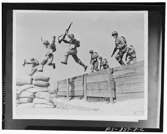 Camp Edwards, Massachusetts. A hard-running leap takes these artillerymen over one of the obstacles on the obstacle course at the anti-aircraft training center. Here we see the different phases of the jump; one man has just landed on the sandbags; two are in the air; and another man is gathering himself for the spring across
