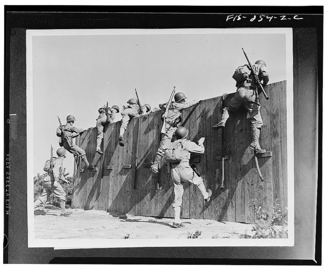 Camp Edwards, Massachusetts. Up and over an eight-foot wall go seven soldiers of the anti-aircraft training center. The ropes are used only by the shorter warriors who cannot otherwise reach the top. Note the full equipment on each soldier