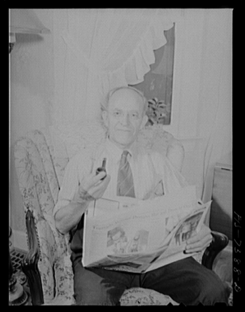 Cass Lake, near Pontiac, Michigan. Karl Axel Westerberg relaxing with the evening paper at his home after a day's work at the Johansson gauge division of the Ford Motor Company, where he is foreman of the rough stock department