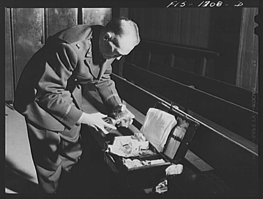 Chaplain Joseph W. Ruane, packing his mass kit after saying Mass. This kit contains all the necessary articles and vestments needed during the Catholic religious services. Many of these kits are distributed by the Chaplain's Aid Association of New York, and are built for compactness and portability. U.S. Army Chaplain School, Fort Benjamin Harrison, Indiana