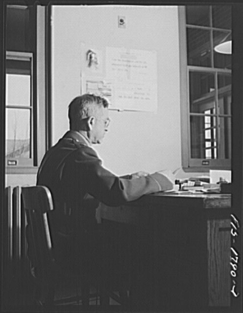 """Chaplain (Lieutenant Colonel) M.D. Merchant, instructor in """"morale,"""" preparing for a class in his office. U.S. Army chaplain school, Fort Benjamin Harrison, Indiana"""