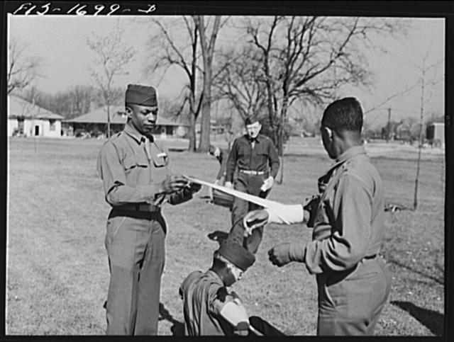 Chaplain Lorenzo Evans removing a bandage from Chaplain Joseph R. Middleton after a first aid class at the U.S. Army chaplain school. Fort Benjamin Harrison, Indiana