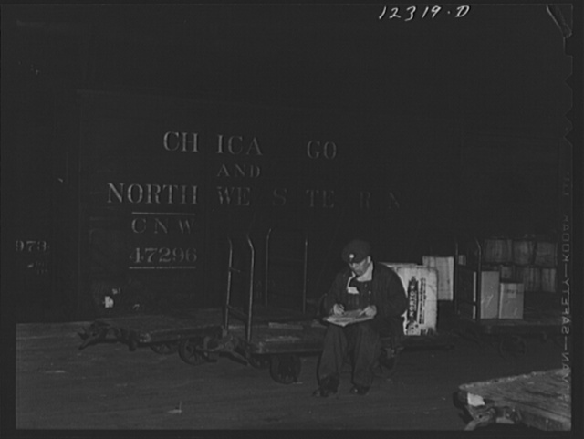 Chicago, Illinois. A checker getting his list ready for loading a car in the freight house of a Chicago and Northwestern Railroad yard