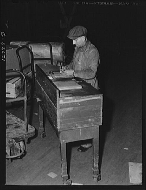 Chicago, Illinois. A checker working at his portable table. These tables are moved about from car to car as each is loaded in the freight house at a Chicago and Northwestern Railroad yard