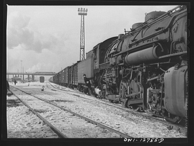Chicago, Illinois. An Indiana Harbor Belt Line railroad engine delivering a trainload of stock and other cars at a yard of the Chicago and Northwestern Railroad. Riding with the engine is the headman