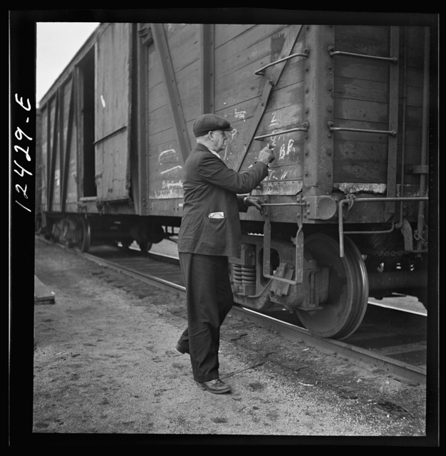 Chicago, Illinois. Car checker writing instructions in chalk for special handling of cars going over the hump at a Chicago and Northwestern Railroad yard