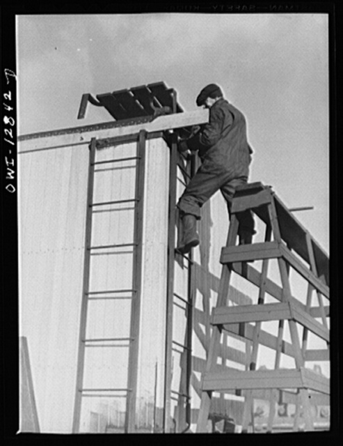 Chicago, Illinois. Carpenter working on a car being rebuilt at the rip tracks at a Chicago and Northwestern Railroad