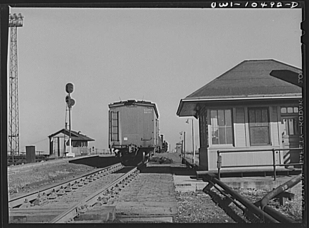 Chicago, Illinois. Cars coming over the south hump at an Illinois Central Railroad yard. Cars are checked by an engine foreman in the building on the right and weighed as they pass by a weighmaster in the building on the right