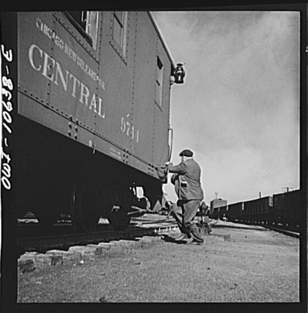 Chicago, Illinois. Conductor hopping aboard the caboose of a southbound freight at an Illinois Central Railroad yard