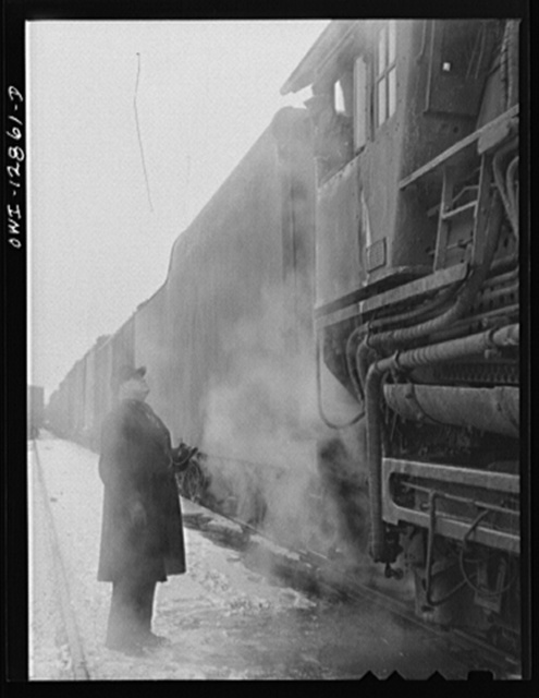 Chicago, Illinois. Conductor John L. Walter comparing time with his engineer before leaving a Chicago and Northwestern Railroad yard for Clinton, Iowa