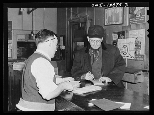 Chicago, Illinois. Conductor John L. Walter getting his waybills before leaving a Chicago and Burlington railroad yard for Clinto, Iowa