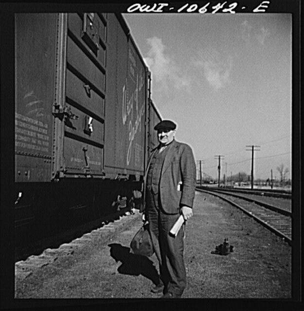 Chicago, Illinois. Conductor waiting to hop aboard the caboose of a southbound freight at an Illinois Central Railroad yard