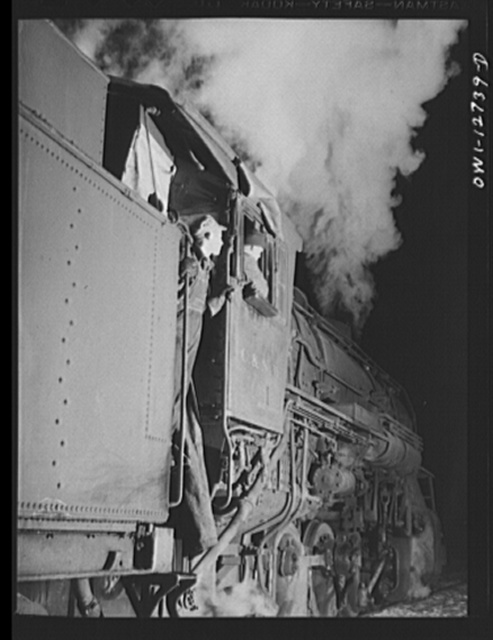Chicago, Illinois. Engineer and fireman on the Chicago and Northwestern Railroad waiting for the highball sign before pulling out of the yard for Clinton, Iowa