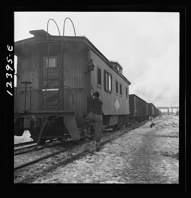 Chicago, Illinois. Freight conductor boarding the caboose of a train bound for the west coast out of Chicago and Northwestern Railroad yard