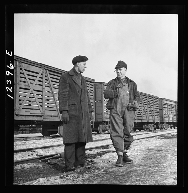 Chicago, Illinois. Freight conductor (right) talking to a yardmaster as he waits for the caboose of his train to come by at a Chicago and Northwestern Railroad yard