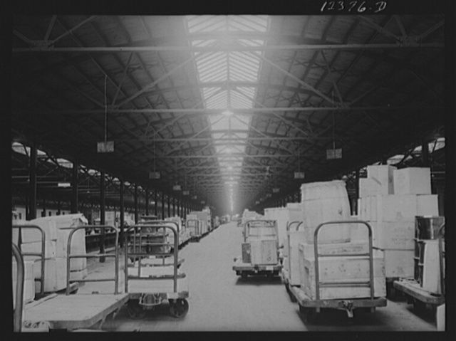 Chicago, Illinois. Goods of every description lined up on loading platforms at a freight house at the Chicago and Northwestern Railroad yard