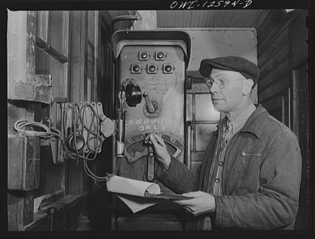 Chicago, Illinois. Hump master in a Chicago and Northwestern Railroad yard operating a signal switch system which extends the length of the hump track. He is thus able to control movements of locomotives pushing the train over the hump from his post at the hump office