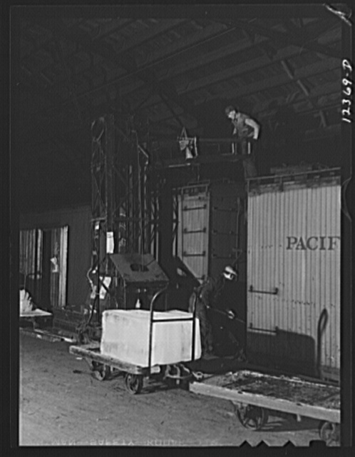 Chicago, Illinois. Icing a refrigerator car in the freight house at a Chicago and Northwestern Railroad yard