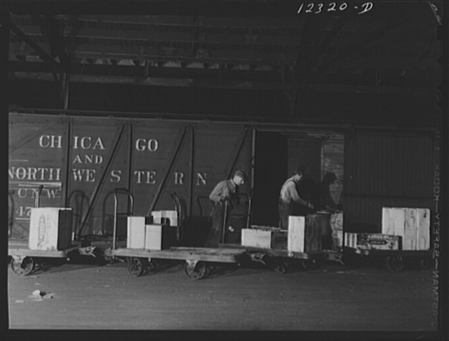 Chicago, Illinois. Loading a freight car in the freight house of a Chicago and Northwestern Railroad yard