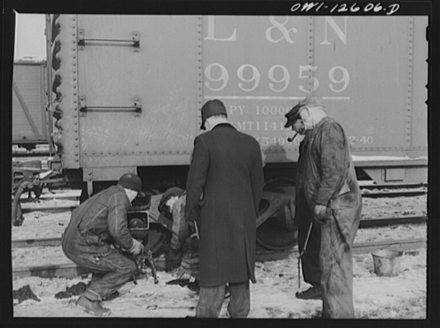 Chicago, Illinois. Making running repairs of a faulty brake shoe which car inspectors have found at a yard of the Chicago and Northwestern Railroad