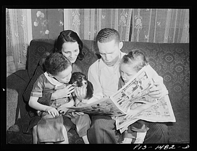 "Chicago, Illinois. On Sunday afternoon at home, ""Red"" Sounders and his wife read the comics to their children and puppy whose name is ""Blitz"""