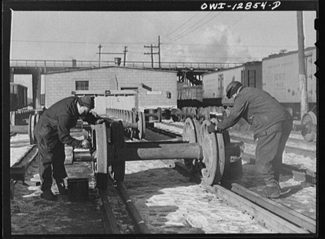 Chicago, Illinois. Painting grease on the bearings of new car wheels just arrived from the shops at the Chicago and Northwestern Railroad rip tracks