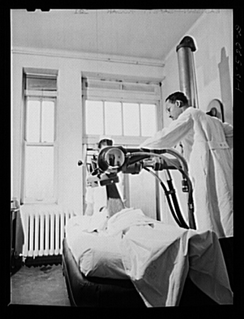 Chicago, Illinois. Provident Hospital. Dr. B.W. Anthony adjusting machine to administer x-ray treatment to a patient