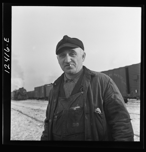 Chicago, Illinois. Railroad worker whose job is to inspect journal boxes, brake shoes, etc. and make minor repairs at a Chicago and Northwestern Railroad yard