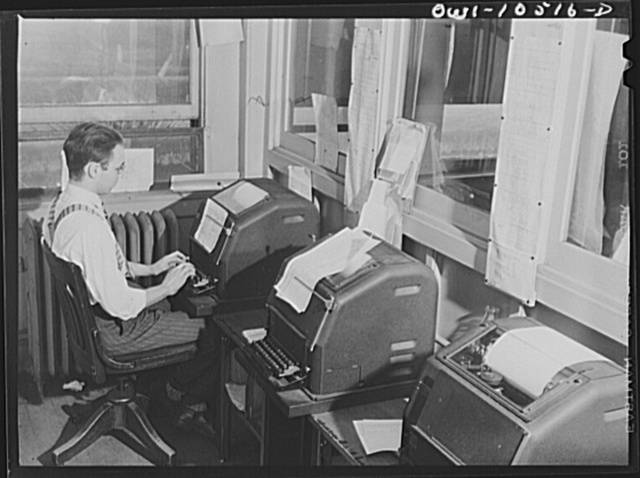 Chicago, Illinois. Switch lists are sent by teletype from the main yard office to yardmasters, tower men, and other offices at an Illinois Central Railroad yard